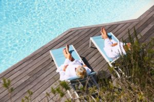 Senior couple relaxing by swimming pool in spa hotel